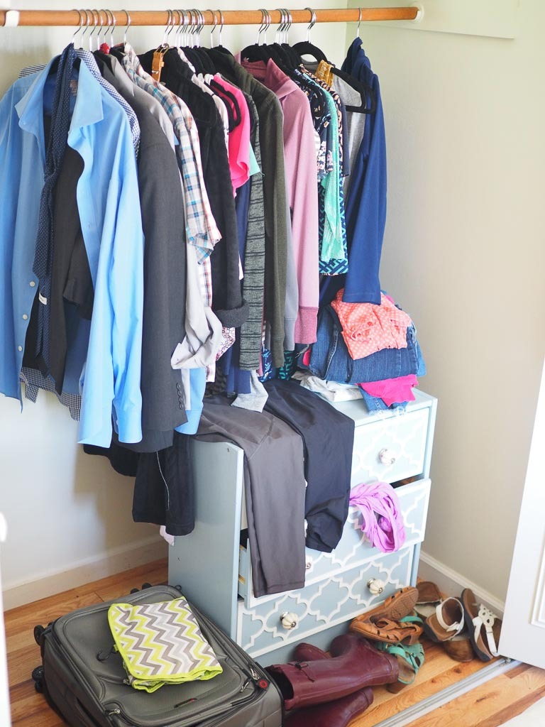 messy closet with clothes out before decluttering