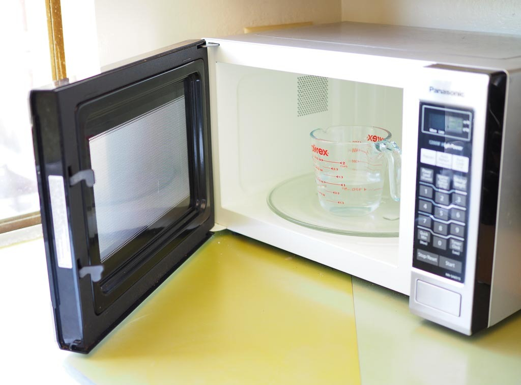 cup of water in microwave ready to warm up for deep cleaning the immersion blender blades