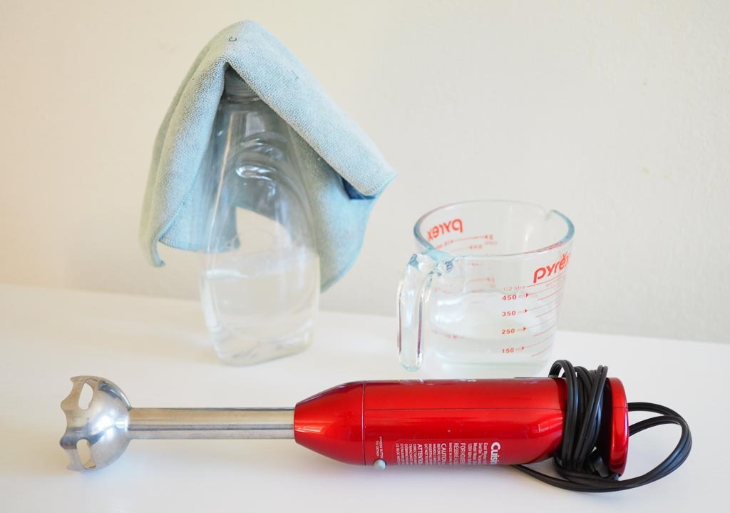 picture of supplies need to deep clean the immersion blender: soap, rag, container, and immersion blender