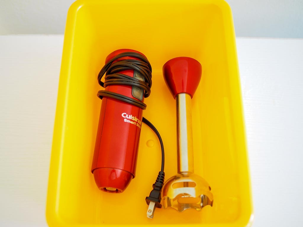 red immersion blender placed in a box